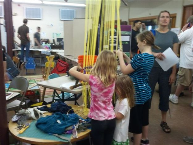 "Photo of kids working on a ""web of life"", working with  natural materials and scraps of cloth from people in the neighborhood at 2012 Sustainability Fair."